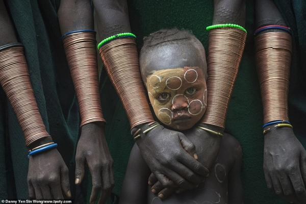 7377444 6491533 a young boy stands among suri women wearing copper bracelets in a 82 1544703332533